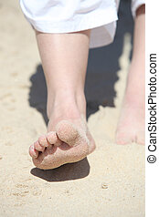 close-up of feet in the sand