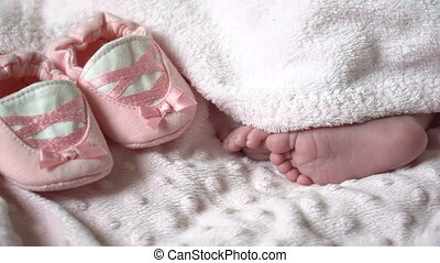 Close-up of feet of a newborn baby. Close-up of legs of a small child