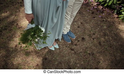 Close-up of feet of a young beautiful couple newlyweds standing in park