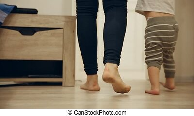 Close-up of feet of mother and baby doing first steps around the house. Feet coming up the stairs.