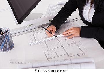 Close-up Of Female Architect Drawing Blueprint