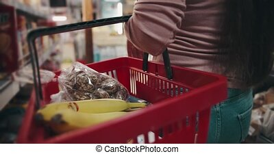 Close up of female customer carrying on red basket full of high quality products at grocery store. Happy woman doing regular shopping of goods at local market