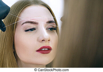 Close-up of female face during eyebrow correction procedure.