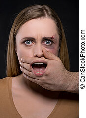 Close up of Female face with covered mouth by male hand and mouth seen through the hand. Concept of woman being attacked and made to be silent when need to shout