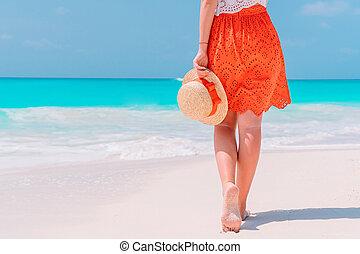 Close up of female feet on white sand beach