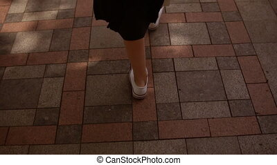 close-up of female feet walking on a concrete pavement