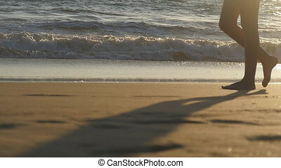 Close up of female feet walking on golden sand at the beach with ocean waves at background. Legs of young woman stepping at sand. Barefoot girl at the sea shore. Summer vacation holiday. Slow motion