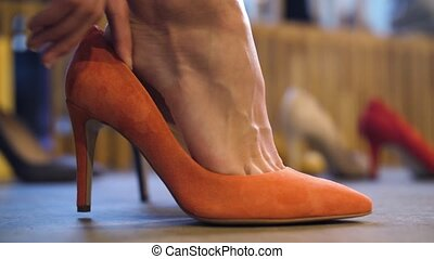 close up of female foot trying shoe at store - sale,...