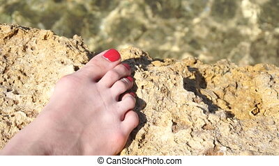 female foot with red nails stands on the rock