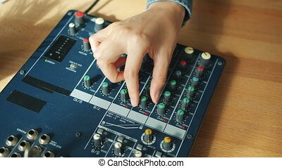 Close-up of female hand adjusting sound quality recording...