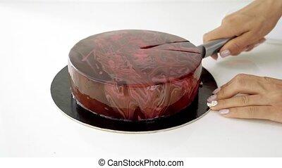Close up of female hand cutting chocolate glaze mousse cake.