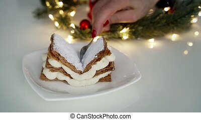 Close up of female hand cutting classic milfey cake with cream in the bowl
