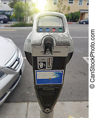 Close up of female hand inserting credit card into parking meter time outdoors on street.