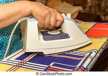 Close-up of female hand ironing