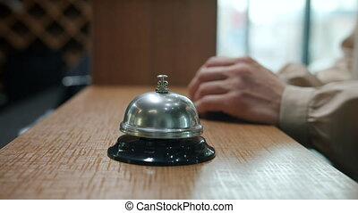 Close-up of female hand ringing reception desk bell then taking key card during check-in in hotel lobby. Travelling and accommodation concept.