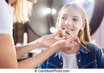 Close up of female hands applying lipstick to girls lips