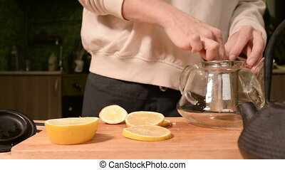 Close-up of female hands are cutting a knife with lemons into pieces and squeezing for making tea on a wooden table of home cooking. Home cooking tea