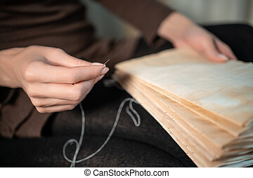closeup of handmade or girl hands making and sew book