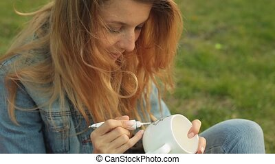 Close-up of female hands drawing a pattern with paint from a tube on a white mug. Smiling girl paints ornament sitting on the grass in the evening.
