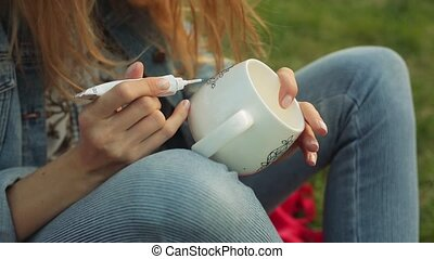 Close-up of female hands drawing flowery pattern on a white cup. Girl paints ornament sitting on the grass in the evening.