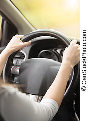 Close-up of female hands hold on the steering wheel