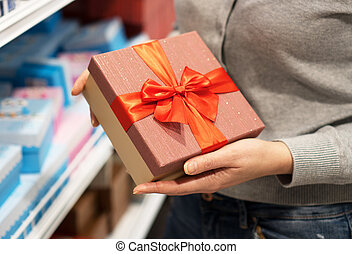 Close-up of female hands holding gift box.