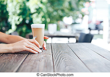Close-up of female hands holding latte