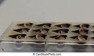 Close-up of female hands making chocolate candies in bakery