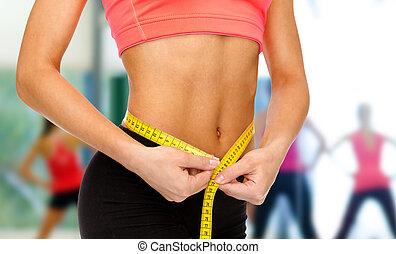 close up of female hands measuring waist