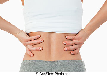 Close up of female hands on hip against a white background