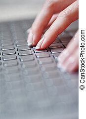 close-up of female hands on the laptop keyboard