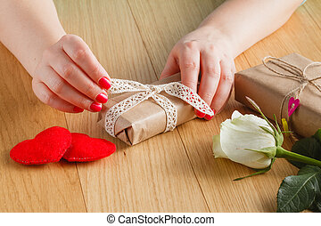 Close-up of female hands packing a small present