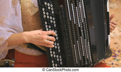 Close-up of female hands playing black accordion - Close-up...