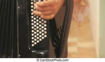 Close-up of female hands playing black accordion