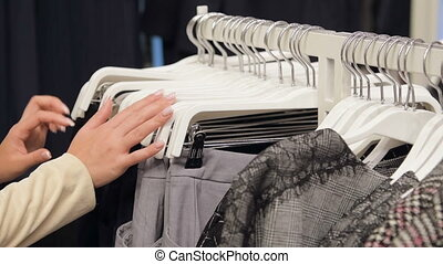 Close-up of female hands plucked a hanger with clothes....