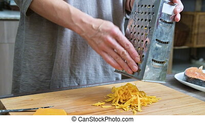 Close-up of female hands rubbing cheese on a metal grater....
