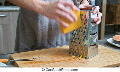 Close-up of female hands rubbing cheese on a metal grater. Cooking in the home kitchen