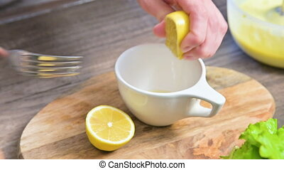 Close-up of female hands squeeze a lemon in a mug on a cutting board in the home kitchen