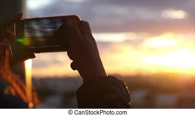 Close up of female hands taking photo of sunset city view...