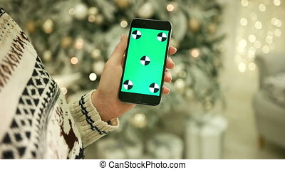 Close-up of female hands touching green screen on mobile phone. Chroma Key. Close up. Tracking motion. Vertical.with blur christmas decoration background