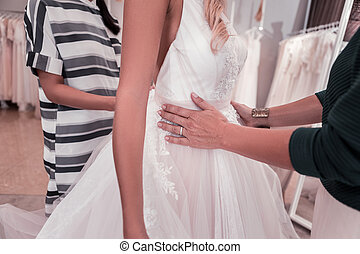 Close up of female hands touching the wedding dress -...