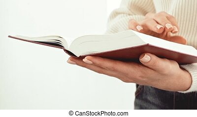 Close up of female hands turning pages of a book