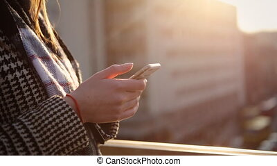 Close up of female hands using smartphone on the balcony of her apartment.