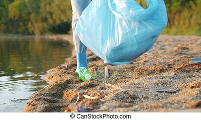 Close-up of female legs and hands collecting garbage on the lake shore in summer