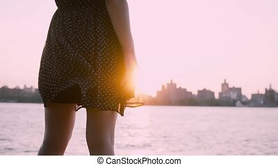 Close-up of female legs in black dress waving in the wind stand at beautiful clear summer cityscape sunset slow motion.