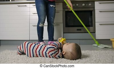 Close-up of female legs mopping floor with baby