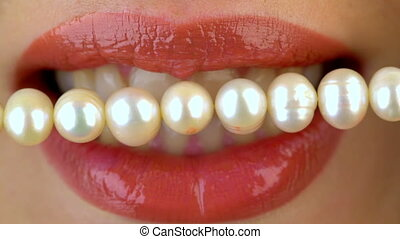 Close up of female lips and pearl bead. Dental concept. -...