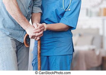 Close up of female nurse helping elderly patient to walk