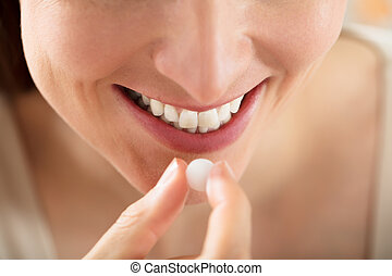 Close-up Of Female Taking White Pill