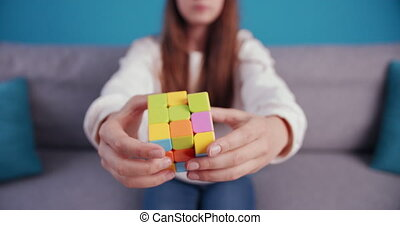 Close up of female teenager playing with Rubik's Cube - ...
